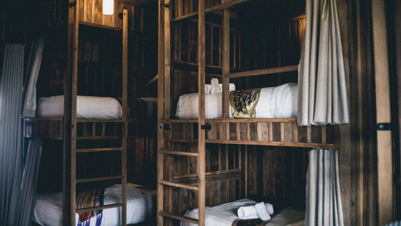 2 bunk beds side by side with a modern looking timber frame, white curtain on each bed, and white sheets
