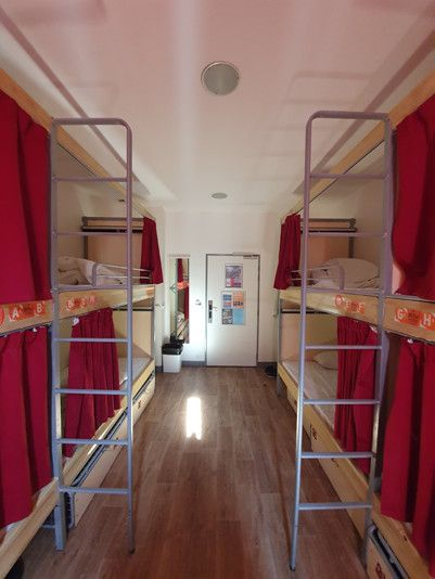 4 bunk beds with ladders leading up to each top bunk, red curtains over each bed