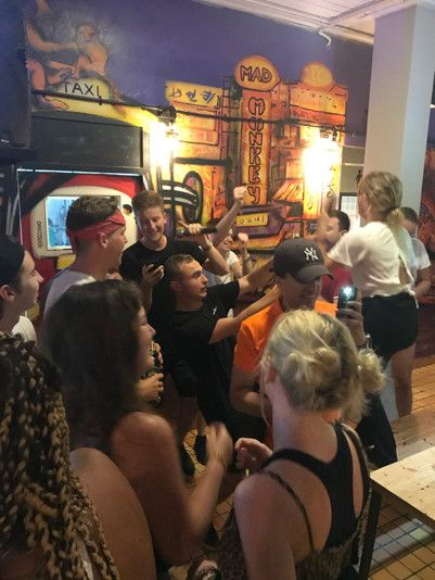 Multiple young people partying and doing karaoke while other take pictures in a bar setting